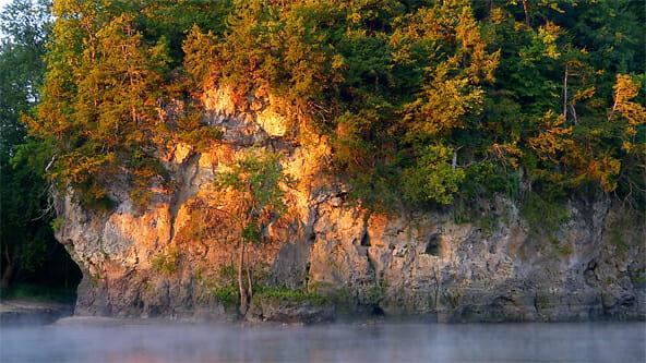 Early morning light illuminates limestone cliffs along the Cedar River in Cedar RApids, Iowa