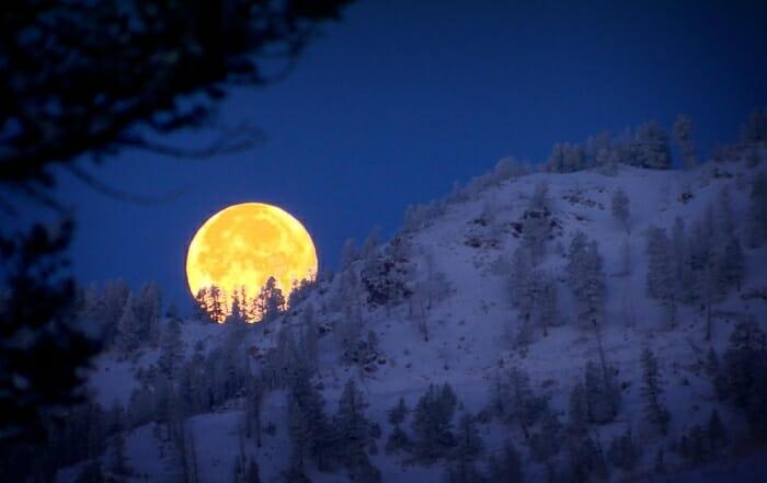 moon setting behind the bridge mountain in Montana