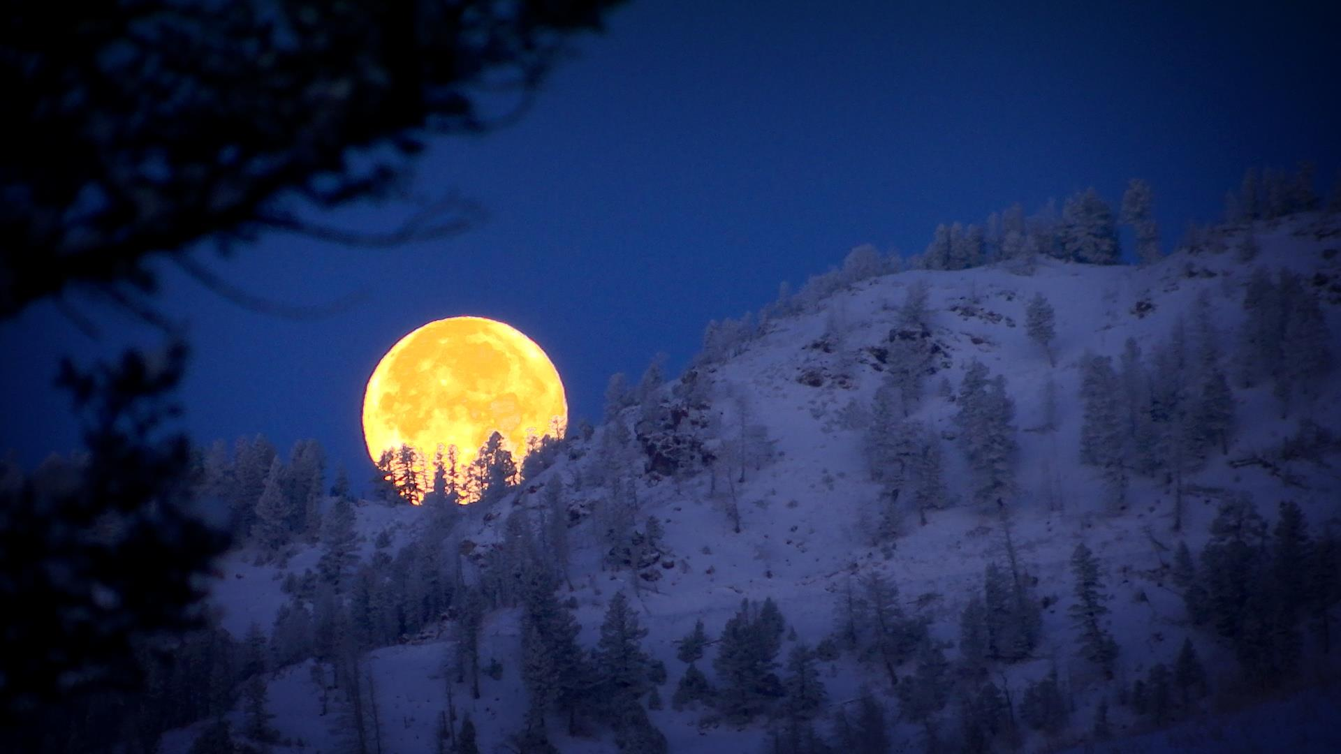 moon setting behind the bridge mountain in Montana